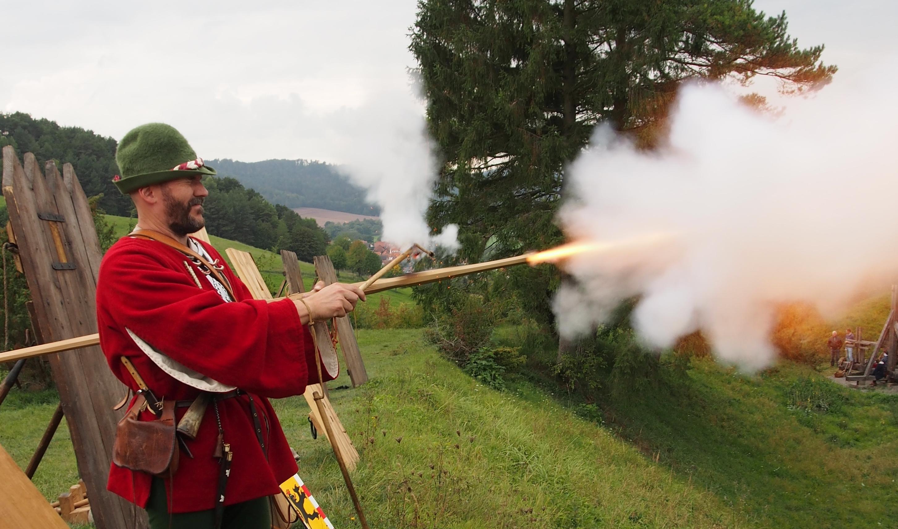 Der Schuß geht los und ein Feuerstrahl und eine Rauchwolke schießen aus der Mündung